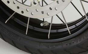 Honda X-ADV  2017 Bild 6 17 Zoll vorn und 15 Zoll hinten, mit rostfreien Edelstahlspeichen, blockprofilierten Reifen und gewinkelten Ventilen. Zwei gegenüberliegende, radial befestigte Vierkolben-Bremssättel greifen an die Bremsscheiben mit 310 mm Durchmesser. Diese Bremsanlage verhindert auch bei heftigen Bremsmanövern, dass der Roller ins Schleudern kommt.