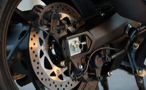Yamaha TMAX 2017 Test Bild 10 Die hydraulische Hinterbremse ist ebenfalls leicht zu dosieren und streng in der Wirkung. Ebenfalls im Bild: Die mechanische Feststellbremse welche über einen Seilzug am linken Lenkerende fixiert werden kann. Somit kann man den TMAX auch problemlos bergab parken.