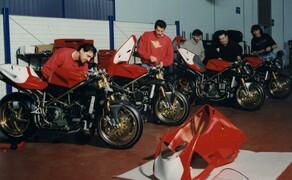 Throwback: Originale Studiobilder der Ducati 916, 996 und 998 Bild 3 Die Mode lässt keinen Zweifel, dass dieses Bild aus 1994 stammt. Damals montierten die Angestellten des Ducati Werks noch mit Schnauzer und Dauerwelle.