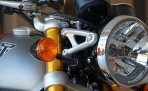 """Triumph Thruxton RS Test 2020 Bild 9 Die Thruxton-Modelle von TRIUMPH können auf eine lange Historie zurückblicken. Sie startete im Jahr 1965, als TRIUMPH begann, eine Kleinserie von rennstreckentauglichen Motorrädern herzustellen. Diese """"Production Racer"""" aus der Rennabteilung der Marke besaßen den Namen """"Thruxton Bonneville"""" und waren im Rennsport überaus erfolgreich. Legendär wurde ein Dreifachsieg dieser Bikes im Jahr 1969 – passenderweise beim 500-Meilen-Rennen auf genau jener Rennstrecke, die als Namenspatin der Thruxton-Renner gedient hatte. Ganz nebenbei waren diese Motorräder mit ihrem """"pure racing style"""" auch die stilistischen Vorbilder für die Café Racer der britischen Motorradszene in den """"Swinging Sixties""""."""